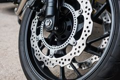 Closeup detail of racing motorcycle disk brake with ABS system and tire on road.  stock images
