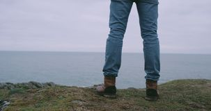 Closeup details of a man tourist wearing a brown boots in the top of mountain shore he admire the ocean view. Closeup details of a man tourist wearing a brown stock footage