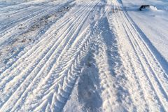 Closeup Details of Tire Marks in Snow on Sunny Winter Day. Abstract Background stock photo