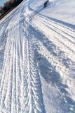 Closeup Details of Tire Marks in Snow on Sunny Winter Day. Abstract Background royalty free stock image