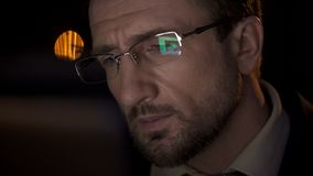 Closeup of detective face, male looking at PC screen reflected in his eyeglasses. Stock photo stock photo