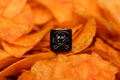 Closeup of dice with skull sketch lying on pile of chips Royalty Free Stock Photo