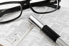 Closeup of dictionary and glasses with pen. Closeup of old dictionary and black glasses with pen royalty free stock photos