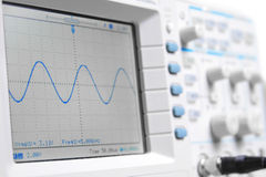 Closeup on a digital oscilloscope showing a sinuso Stock Photos