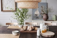 Closeup of dining room table with straw coasters, bread, milk and jam, painting with two cute ducks on the shelf behind it royalty free stock photo