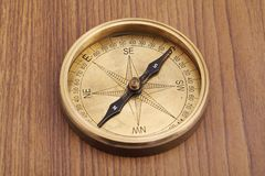 Closeup of directional compass. Closeup of old directional compass on a wooden table stock photography