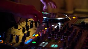 Closeup of disc jockey hands working on mixer in colorful lights of night club