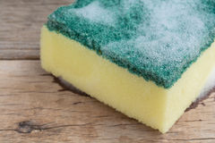 Closeup dishwashing sponge. With foam on wooden background royalty free stock images
