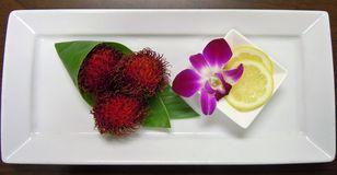 Closeup of a display of Rambutan, lemon slices with an orchid garnish. Amenity display of 3 Rambutan on small rectangular white plate with lemon slices and an stock photos