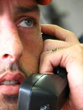 Closeup of Distress. Shot of a young mature man showing half of his face and talking on the phone... The picture is trying to capture his expressions in ONLY stock image