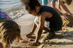 Closeup of diverse kids playing with the sand together at the be. Ach Royalty Free Stock Image