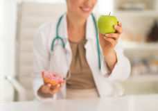 Closeup on doctor choosing between apple and donut Stock Photos
