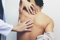 Closeup of Doctor examines or treatment the man with shoulder pain or neck pain on white background,Health concept royalty free stock photos