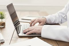 Closeup of doctor hands on laptop keyboard royalty free stock images