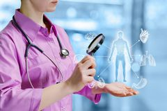 A doctor looking at the human model medical structure through magnifier stock photography