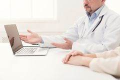 Closeup of doctor and patient sitting at desk stock photography