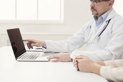 Closeup of doctor and patient sitting at desk stock photos