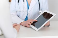 Closeup of a doctor and patient sitting at the desk. Physician pointing into tablet pc. Medicine and health ca. Re concept stock photo