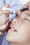 Closeup of doctor pouring eye drops in sick children. Conjunctivitis eyes royalty free stock images