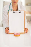 Closeup on doctor showing clipboard and donut Royalty Free Stock Photography