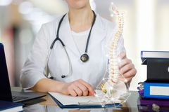 A doctor at the table holding a spin skeleton with pelvis part. A closeup of doctor at table with notebook and patient medical card on it holding a spin skeleton stock photography