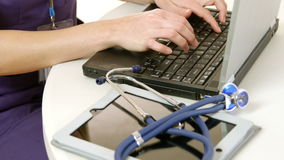 Closeup of doctor typing on a laptop stock video footage