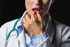 Closeup on doctor woman eating pill isolated on black Stock Photos