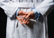 Closeup on doctor woman hiding syringe behind back Stock Images