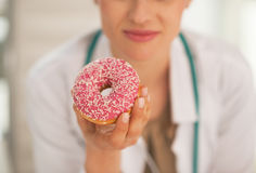 Closeup on doctor woman holding donut Stock Images