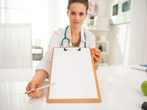 Closeup on doctor woman pointing on clipboard Stock Images