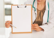 Closeup on doctor woman pointing on clipboard Royalty Free Stock Images