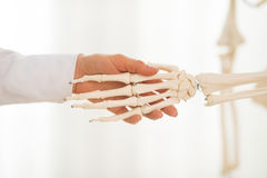 Closeup on doctor woman shaking hands of skeleton Stock Photo
