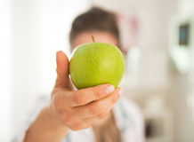 Closeup on doctor woman showing apple. In front of face Royalty Free Stock Photography