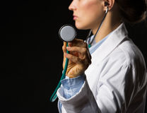 Closeup on doctor woman using stethoscope isolated on black Royalty Free Stock Photos