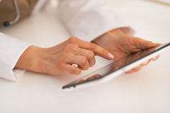 Closeup on doctor woman using tablet pc. At work Stock Photography