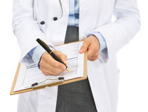Closeup on doctor woman writing in clipboard Stock Photography