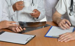 Closeup of doctors hands. Having a discussion at table Stock Images