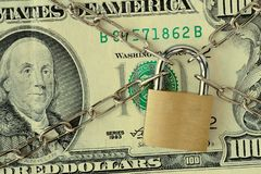 Closeup of dollar banknote locked with chain and padlock - Concept of insurance, bail-in and financial security. Closeup of dollar banknote locked with chain and stock photography