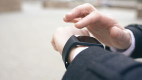 Closeup dolly shot of businessman face and hand using his smartwatch touchscreen standing on the street. Closeup dolly shot of businessman face and hand using stock video footage