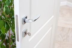 Closeup of door fittings. A white door with modern chrome handles, door lock with key Royalty Free Stock Photos