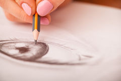 Closeup of drawing human eye at the desk. Closeup of woman`s hands with a pencil drawing human eye at the desk Stock Photo