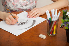 Closeup of drawing human eye at the desk. Closeup of woman`s hands with a pencil drawing human eye at the desk Royalty Free Stock Photography