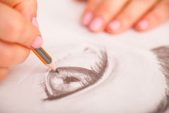 Closeup of drawing human eye at the desk. Closeup of woman`s hands with a pencil drawing human eye at the desk Royalty Free Stock Image