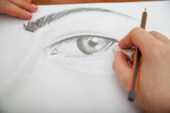 Closeup of drawing human eye at the desk. Closeup of woman`s hands with a pencil drawing human eye at the desk Stock Photography