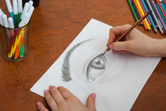 Closeup of drawing human eye at the desk. Closeup of woman`s hands with a pencil drawing human eye at the desk Stock Image