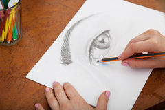 Closeup of drawing human eye at the desk. Closeup of woman`s hands with a pencil drawing human eye at the desk Royalty Free Stock Photos