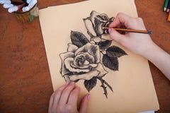 Closeup of drawing roses at the desk Royalty Free Stock Photo