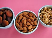 Closeup of dried apricots, almonds and walnut halves in blue bowls on pink background. Three bowls of healthy, nutritious dried fruit and nuts for snacking or stock images