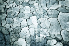 Closeup of a dried cracked desaturated earth soil Stock Photos