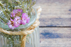Closeup dried flowers in glass jar on blurred wooden table, copy Royalty Free Stock Photo